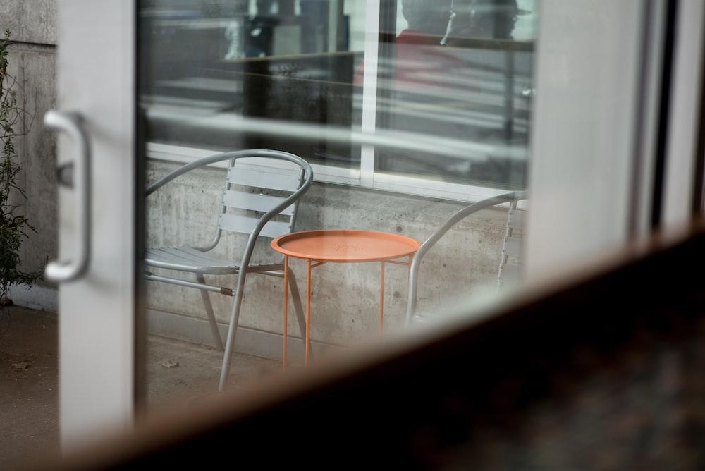 round orange metal table beside gray metal chair