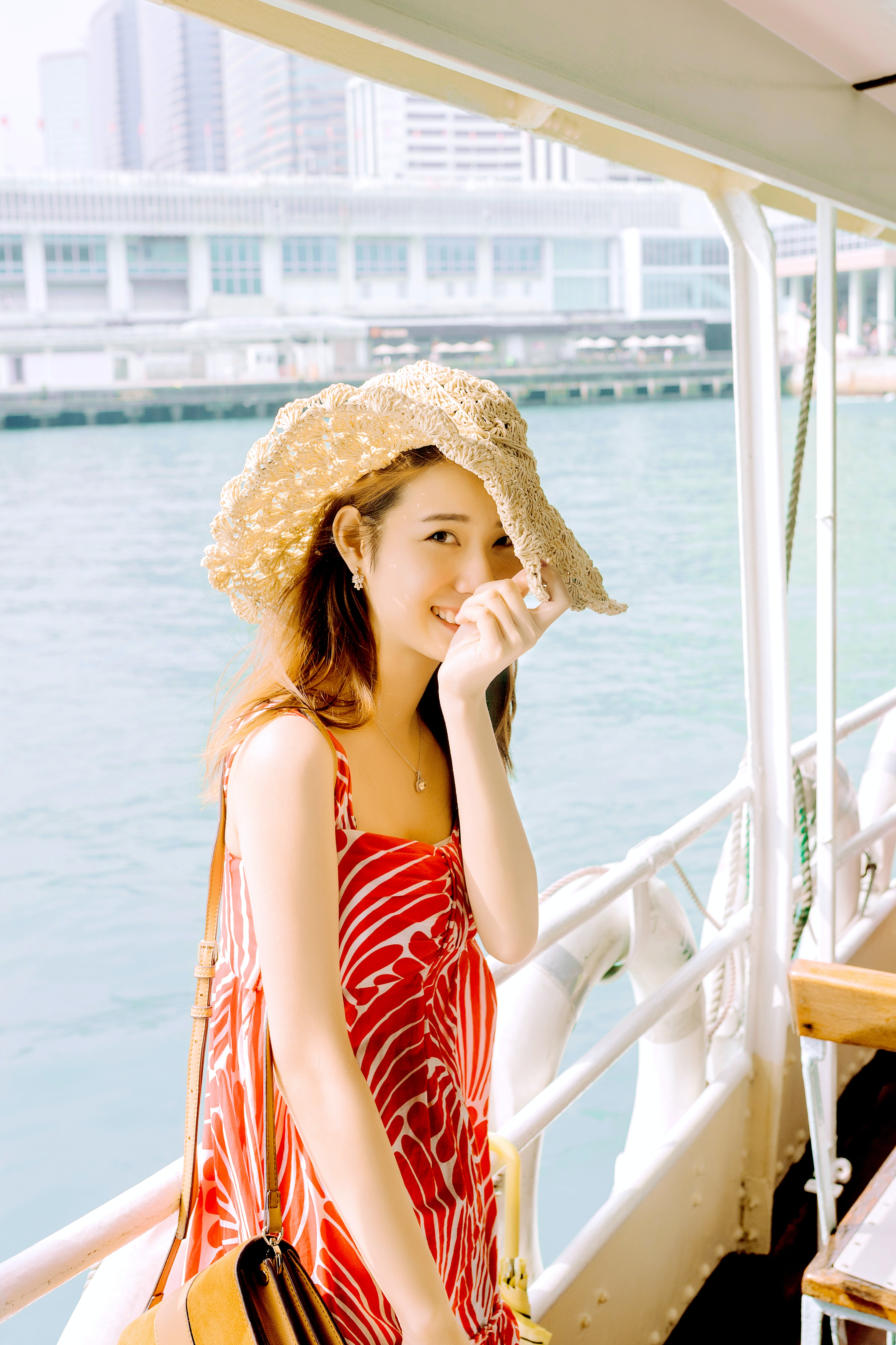 woman wearing red and white scoop-neck sleeveless dress on boat