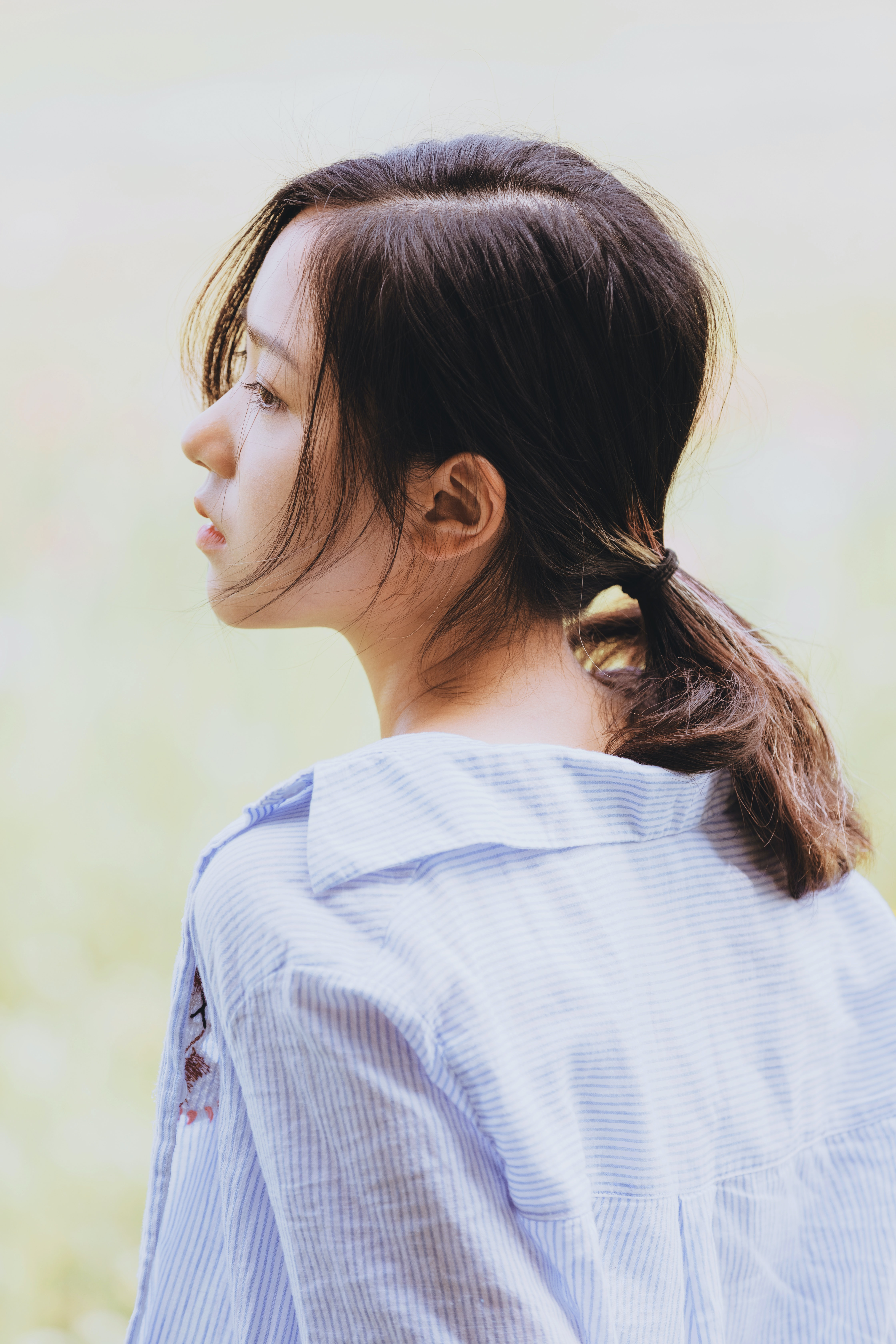 woman wearing blue shirt with pony tail