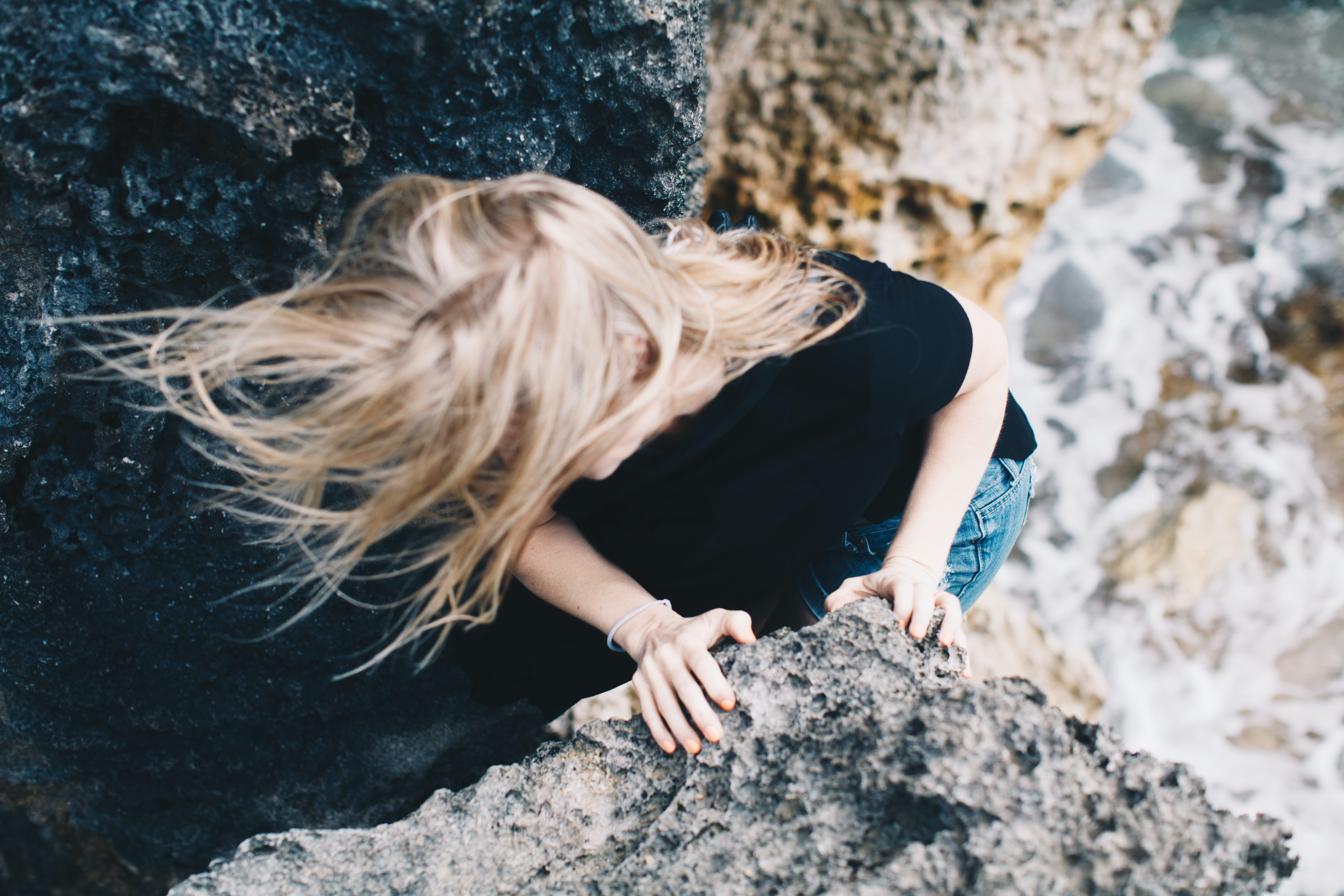 woman climbing on cliff near body of water