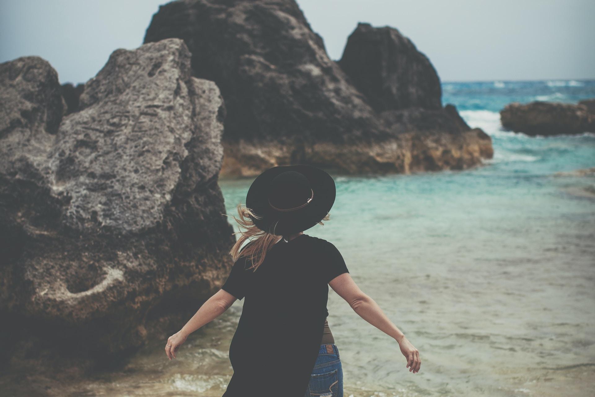 woman standing on rock near ocean shoreline