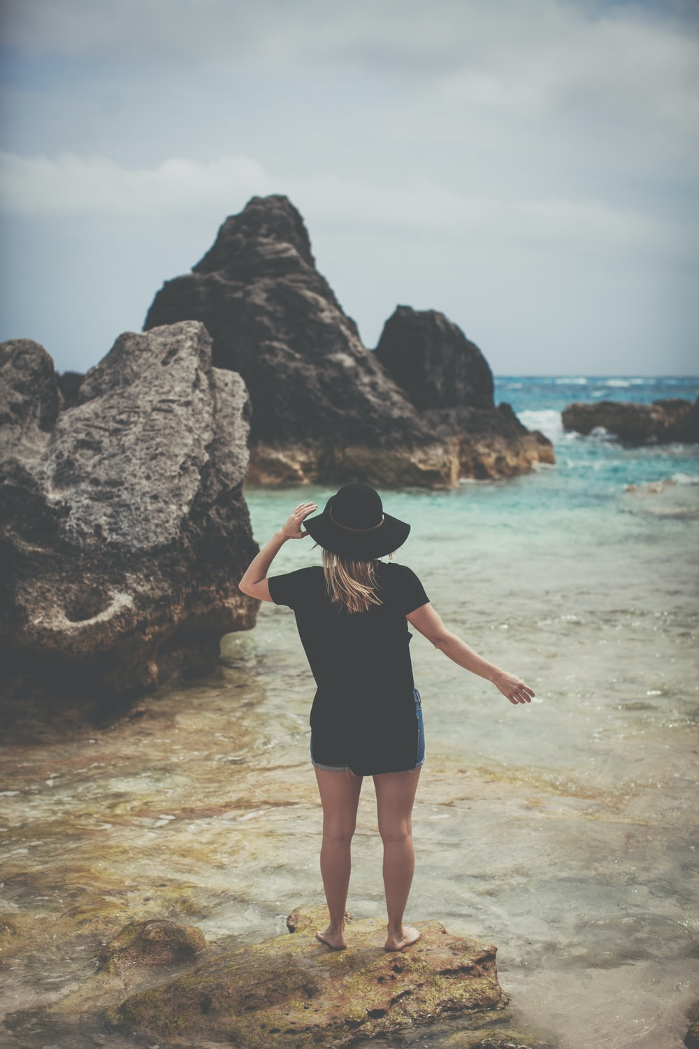 woman standing on rock seeing body of water