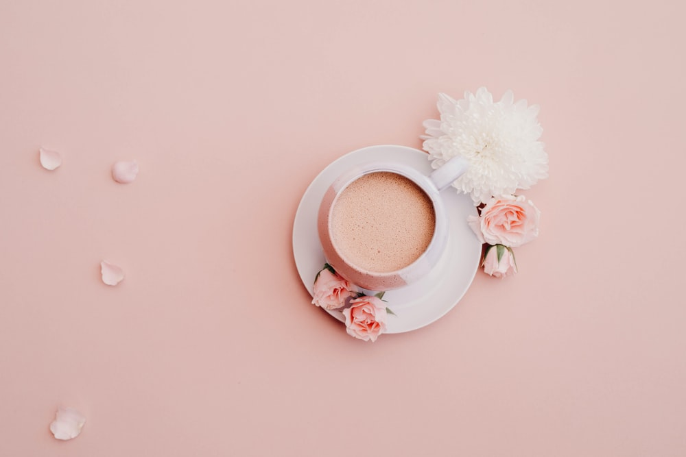 white glazed cup with saucer on pink surface