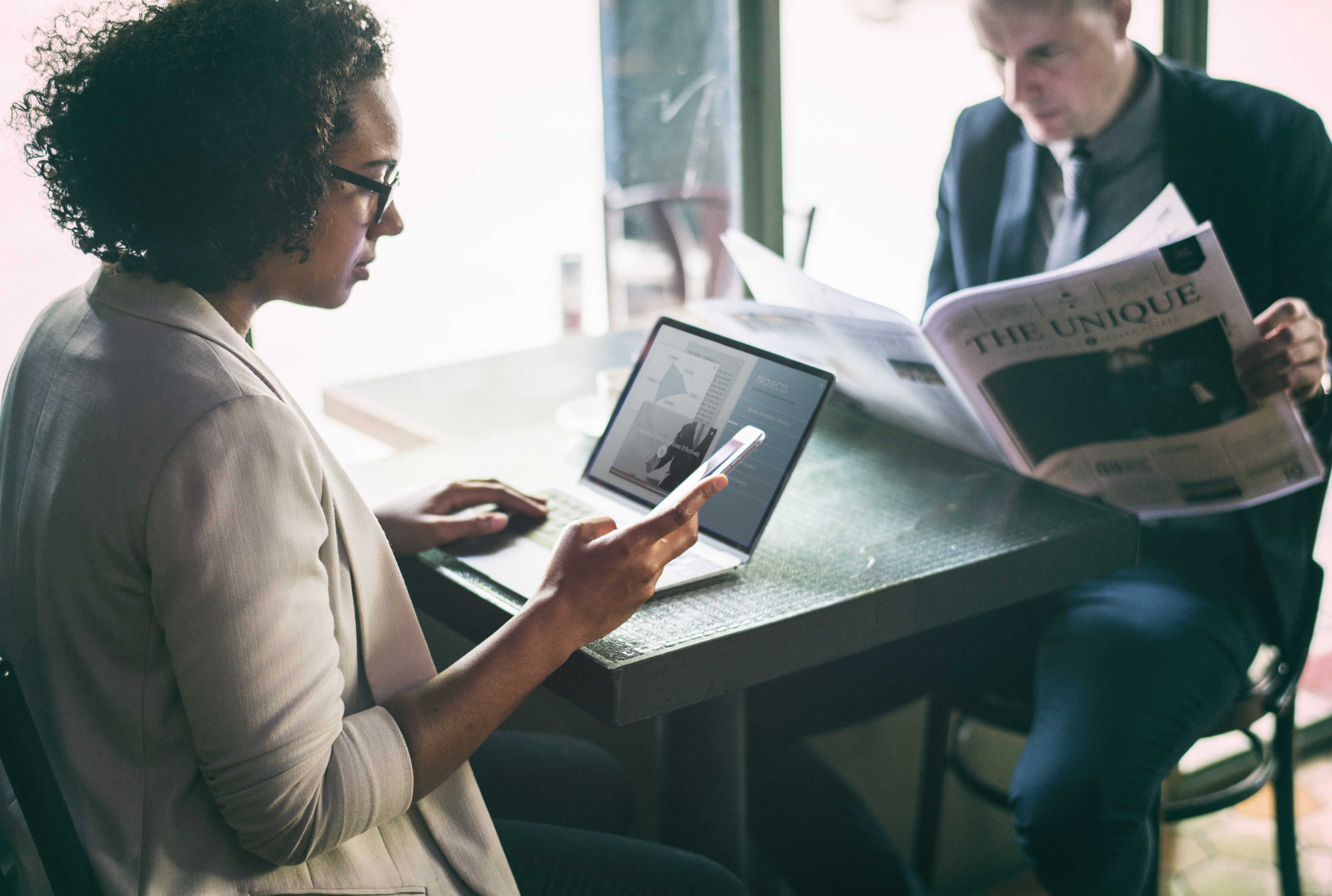 woman using smartphone and laptop in front man reading newspaper