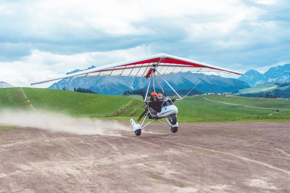 two person riding on paragliding plane