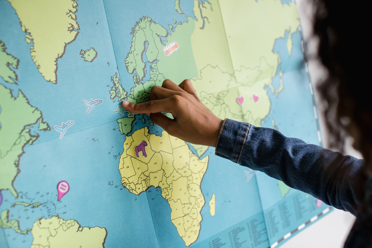 Black female putting travel and airplane stickers on a map