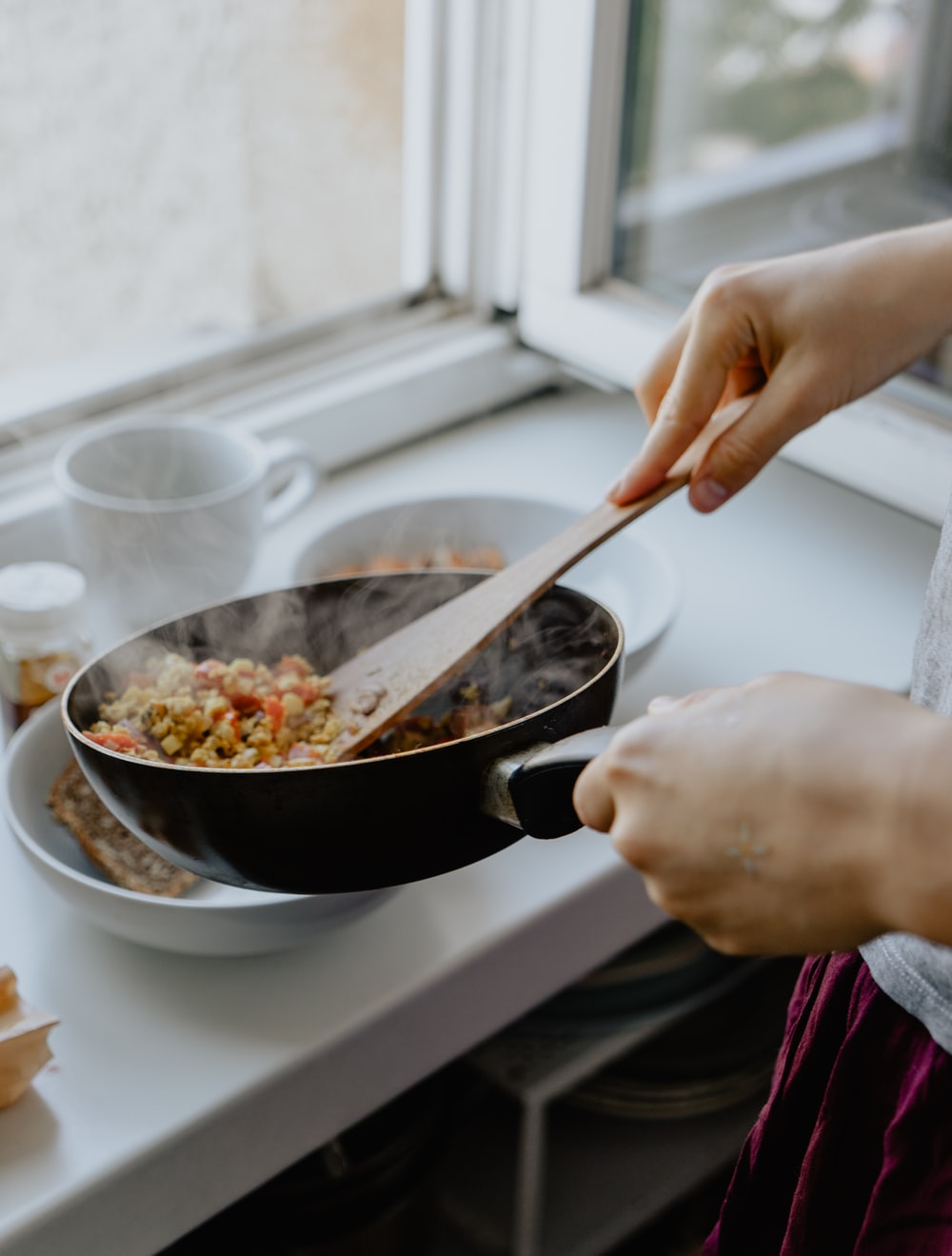 person holding black frying pan