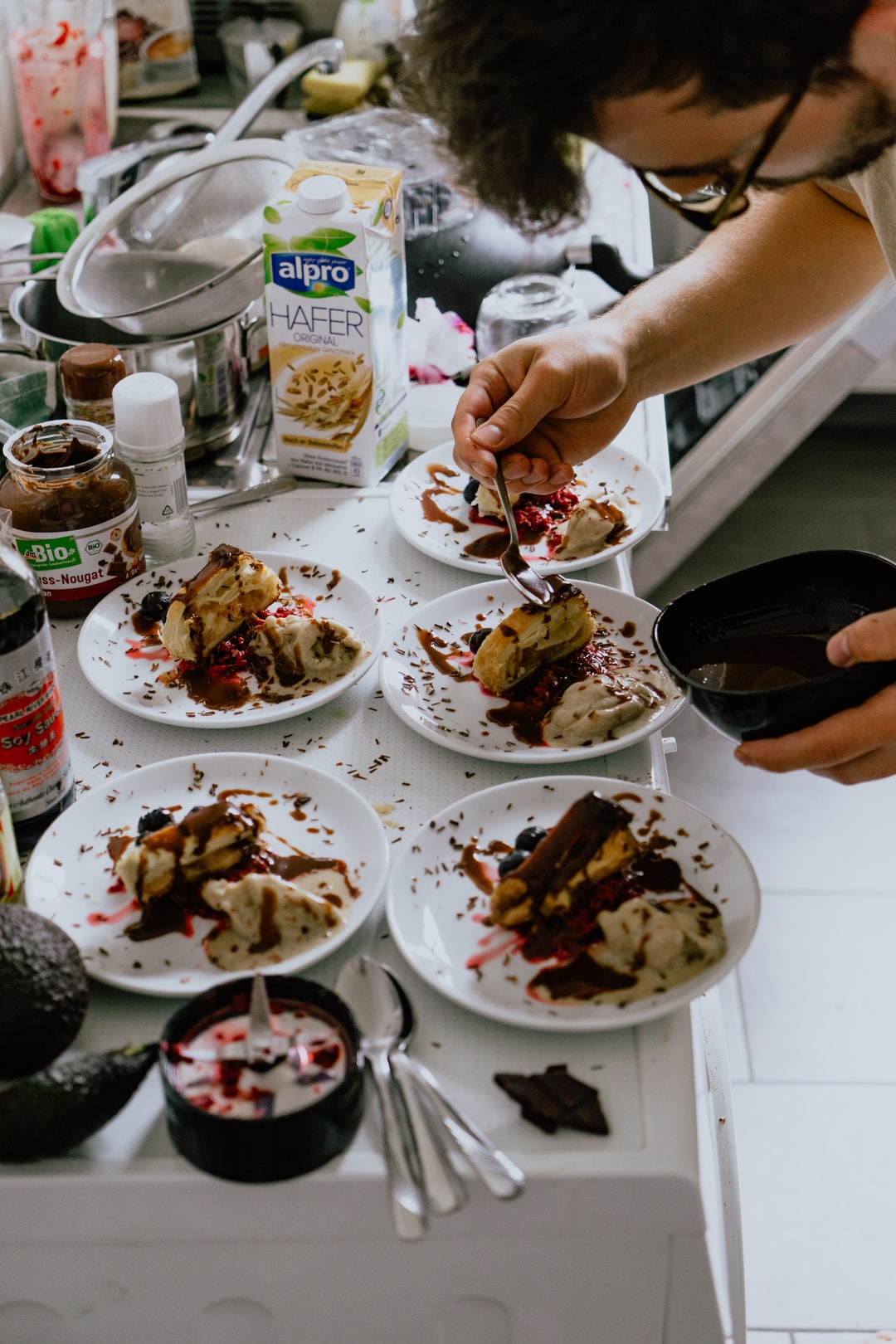 Mid-action shot of Sergej putting together a vegan apple slice and self made frozen banana ice-cream dessert for our guests