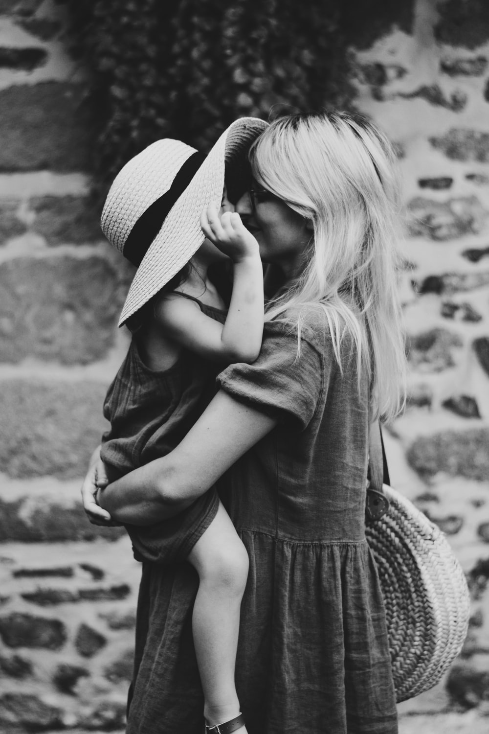 grayscale photography of woman carrying girl