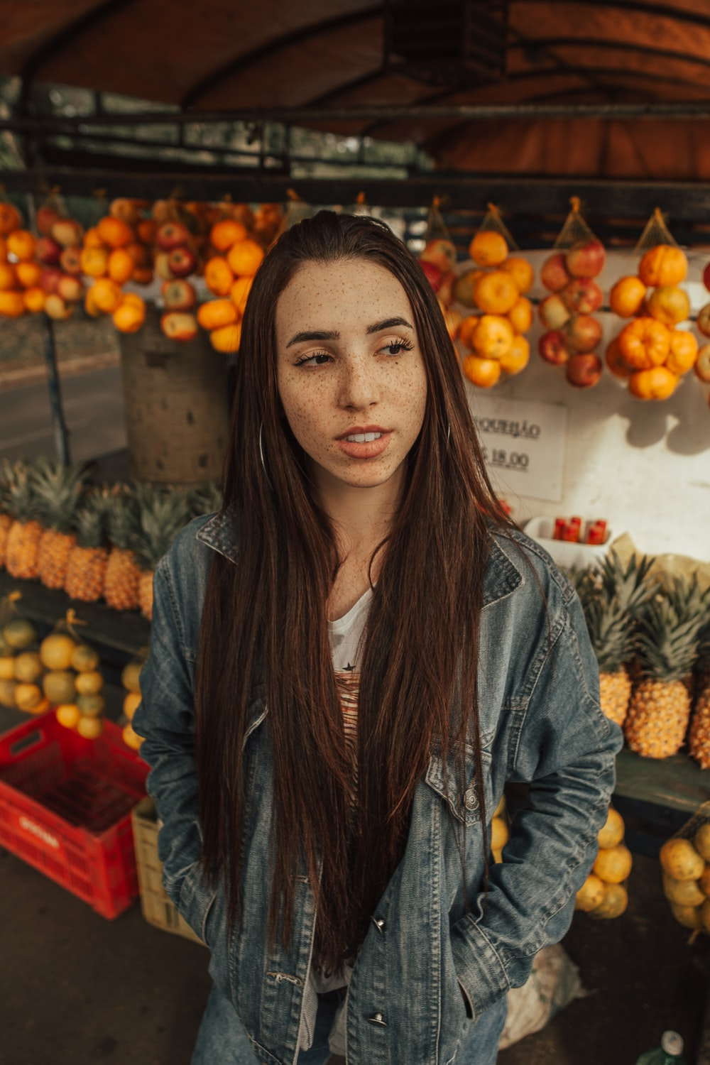 woman wearing blue jacket in fruit store