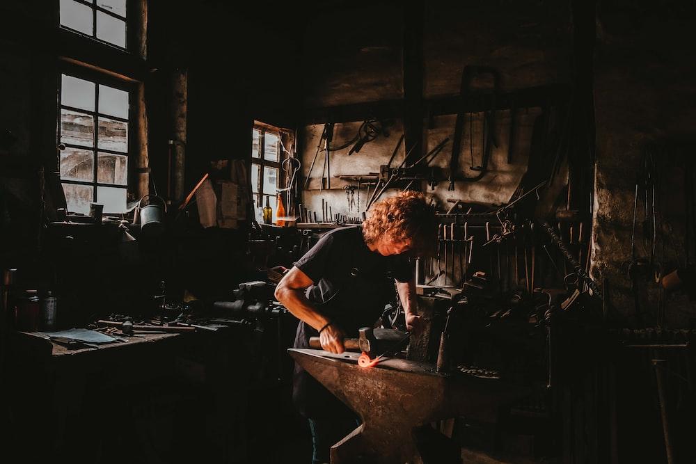 man holding hammer while forging on anvil inside room