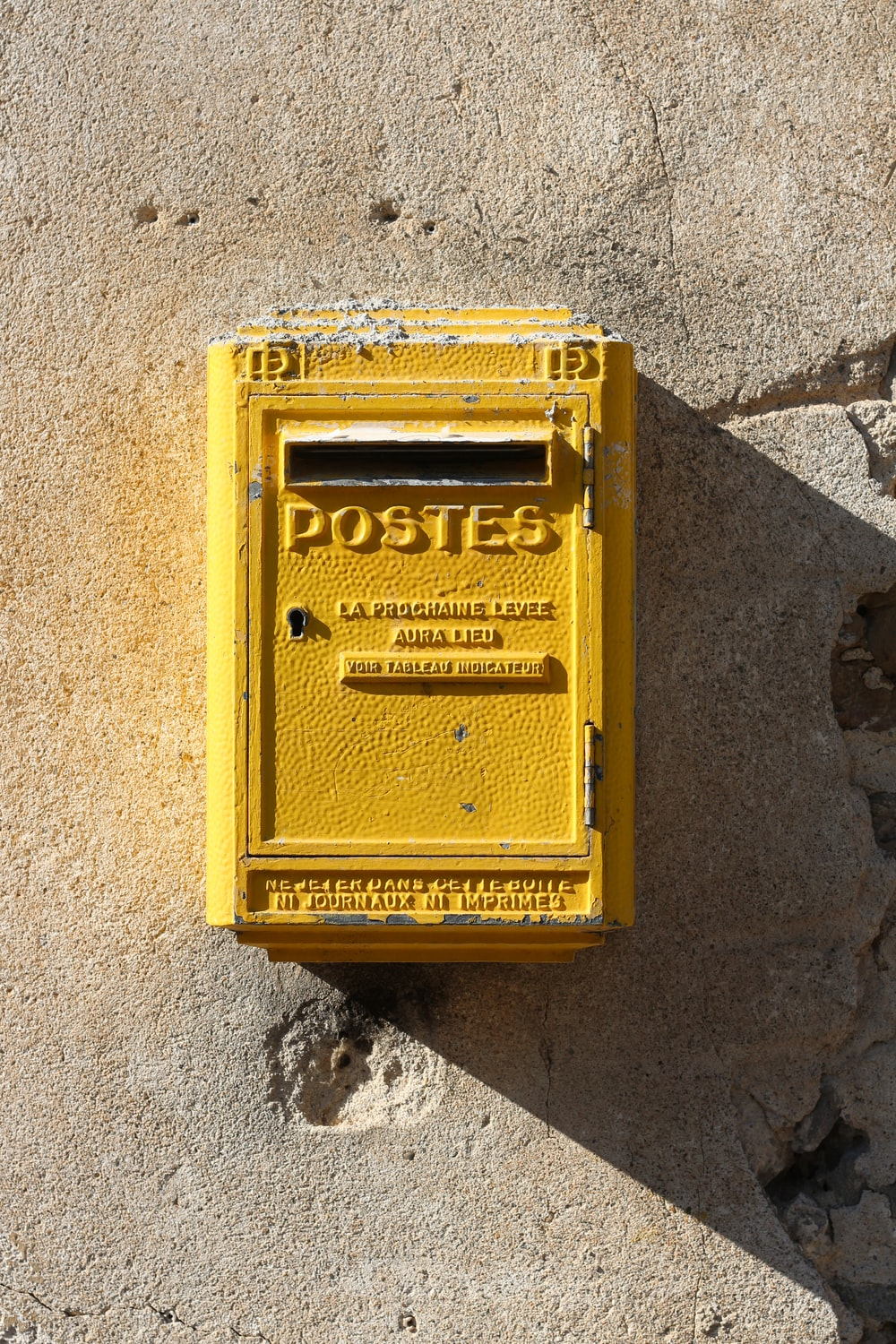 yellow steel mail box mounted on gray wall