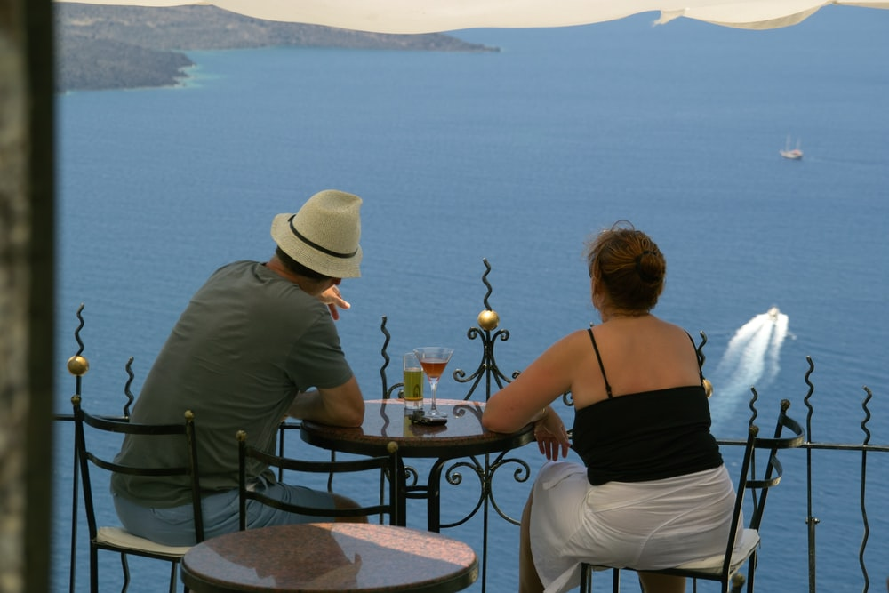 back view of man and woman sitting in front of terrace with sea view