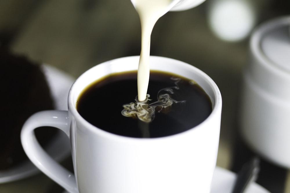 coffee in white ceramic mug while pouring milk