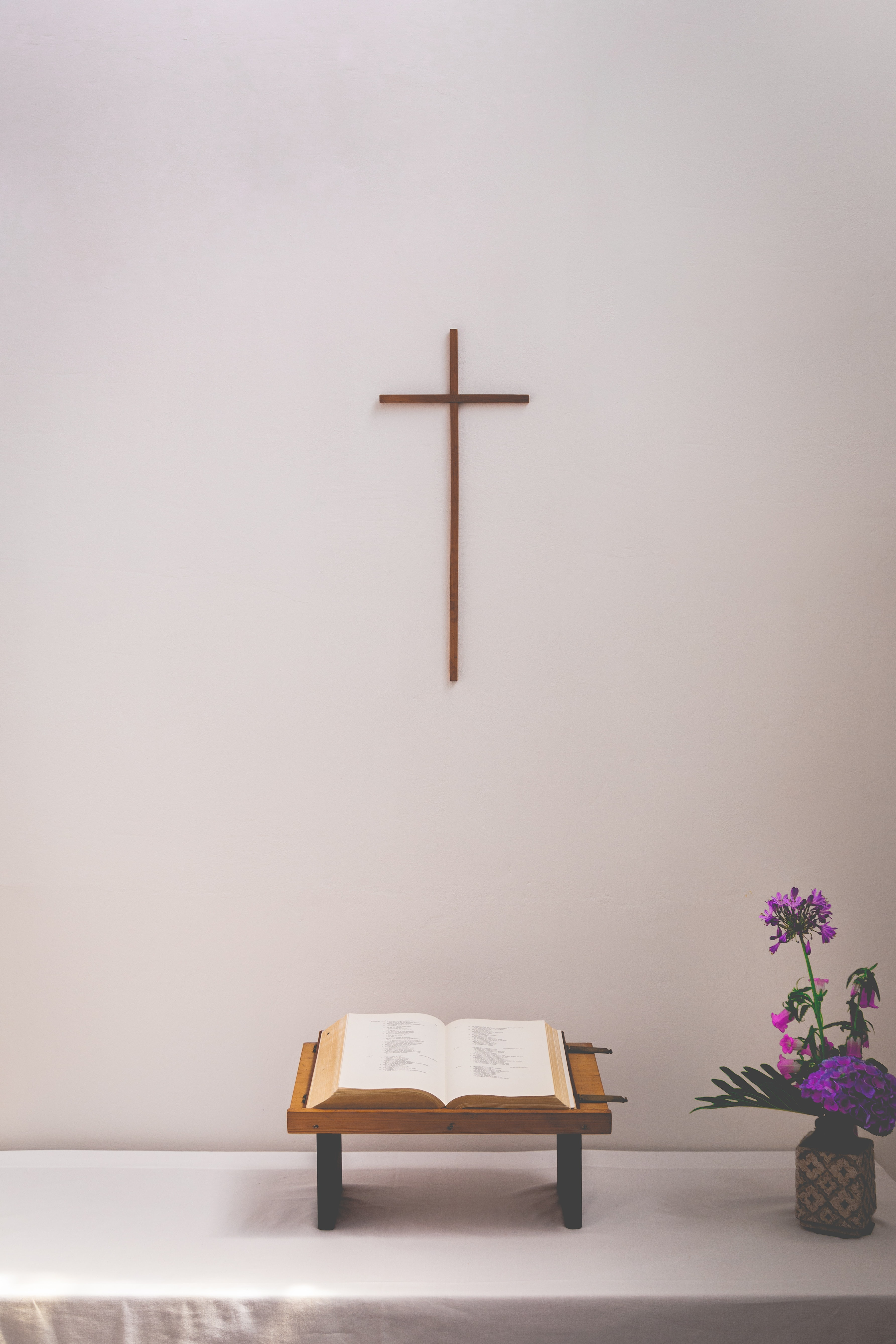 bible on stand under cross on wall