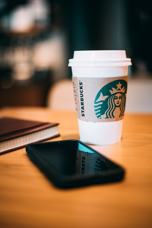 black smartphone beside a white Starbucks cup