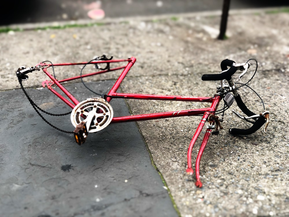 red and black road bike on ground