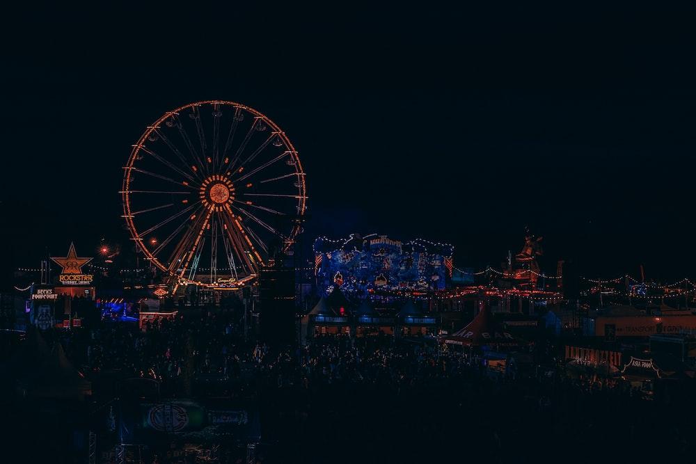 lighted Ferris wheel beside building