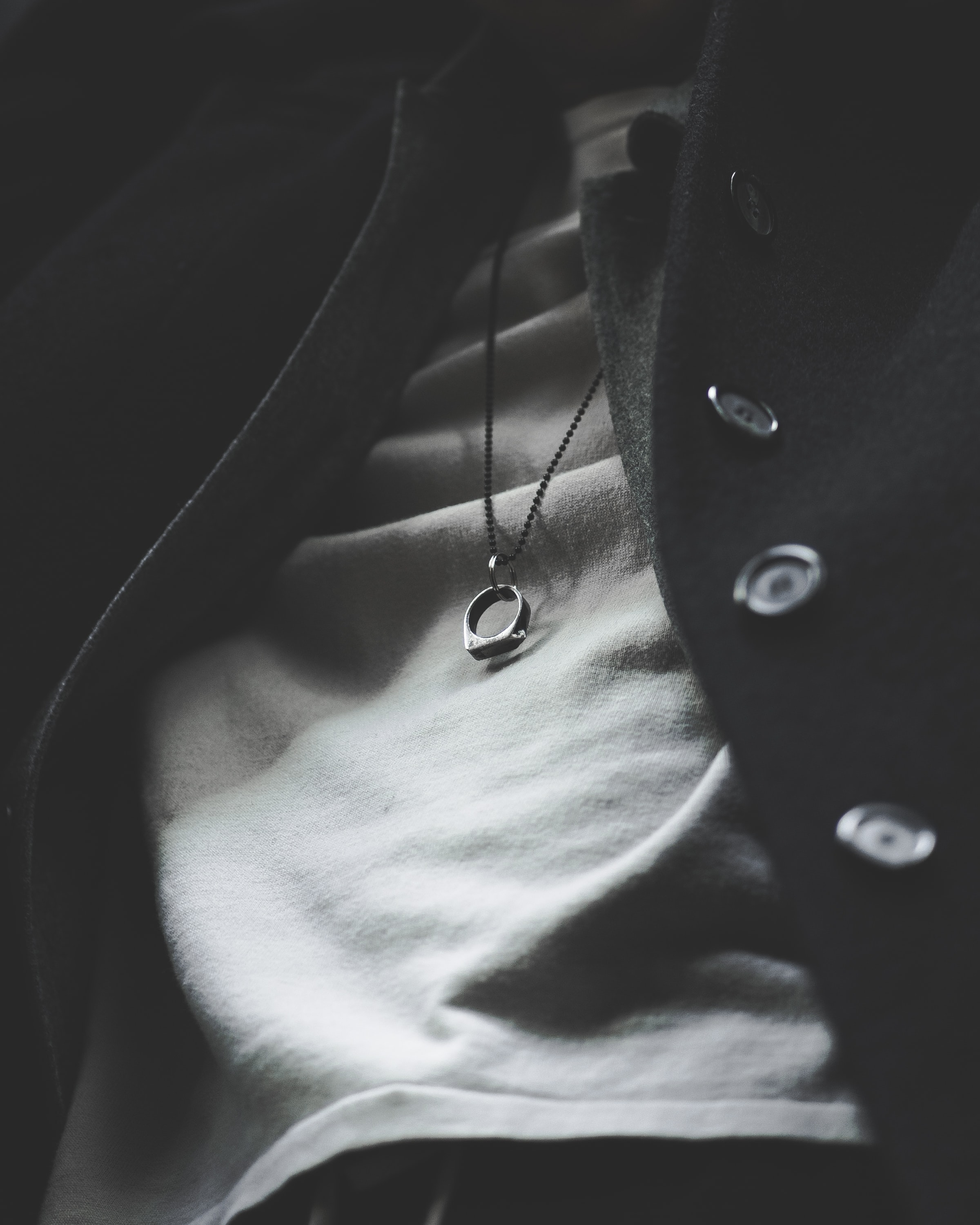 person wearing silver-colored ring pendant necklace in closeup photography
