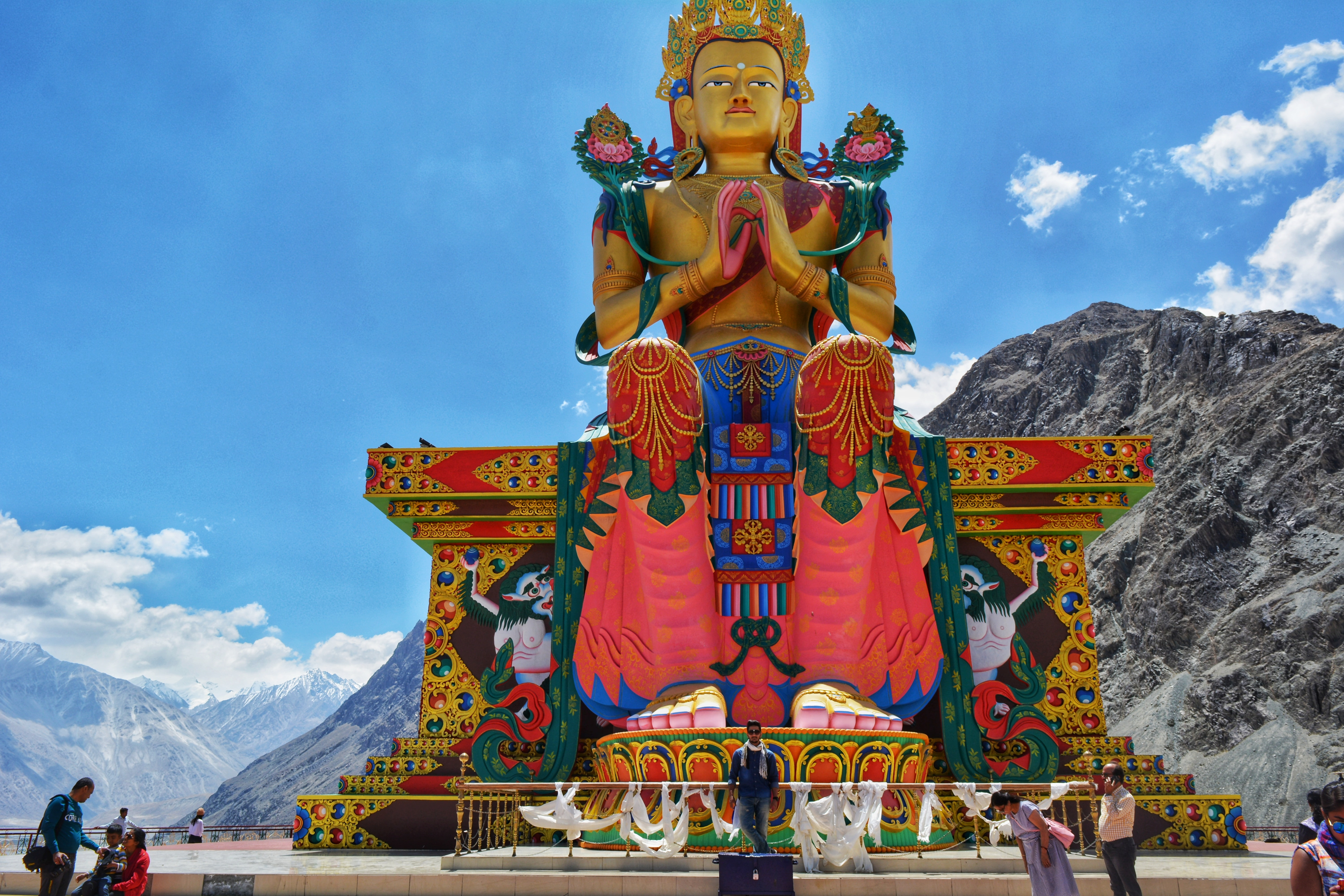 brown buddha statue in front of a mountain