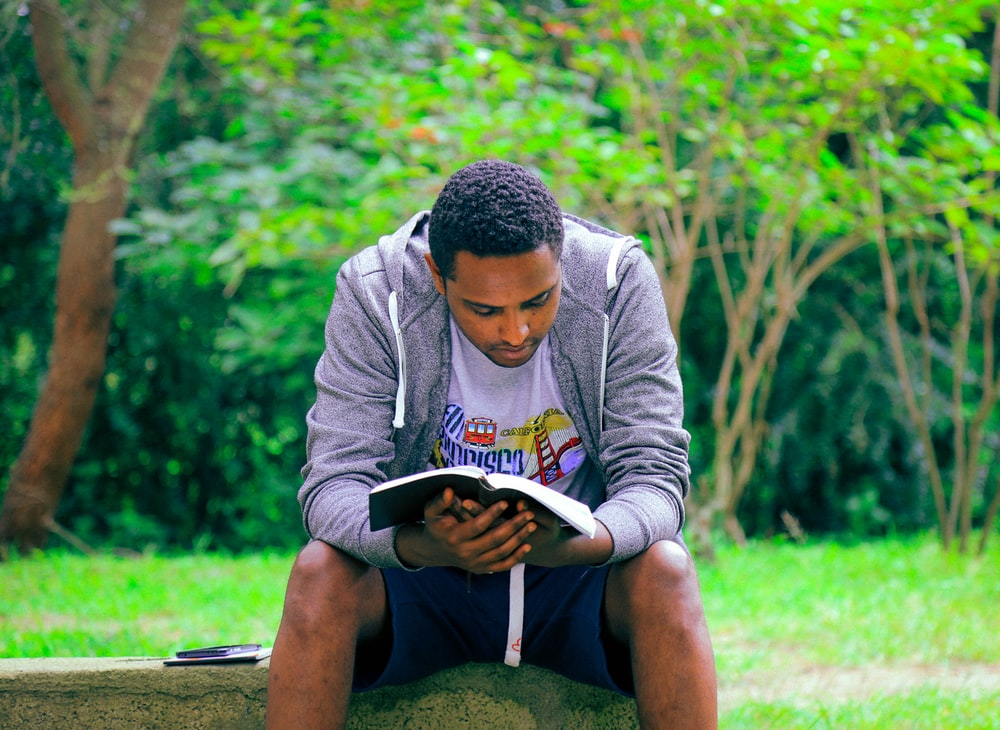 man sitting on concrete bench reading book