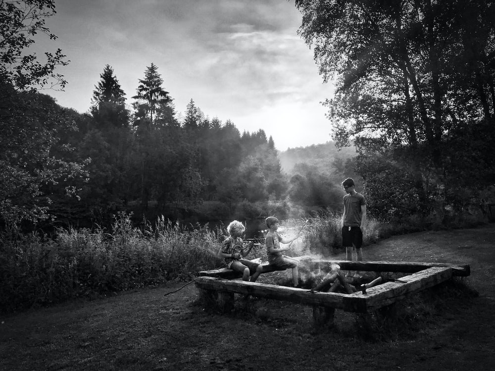 grayscale photo of three person having bonfire near river