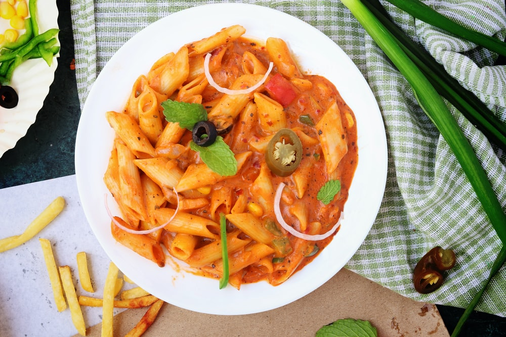 cooked pasta with sauce and pepper