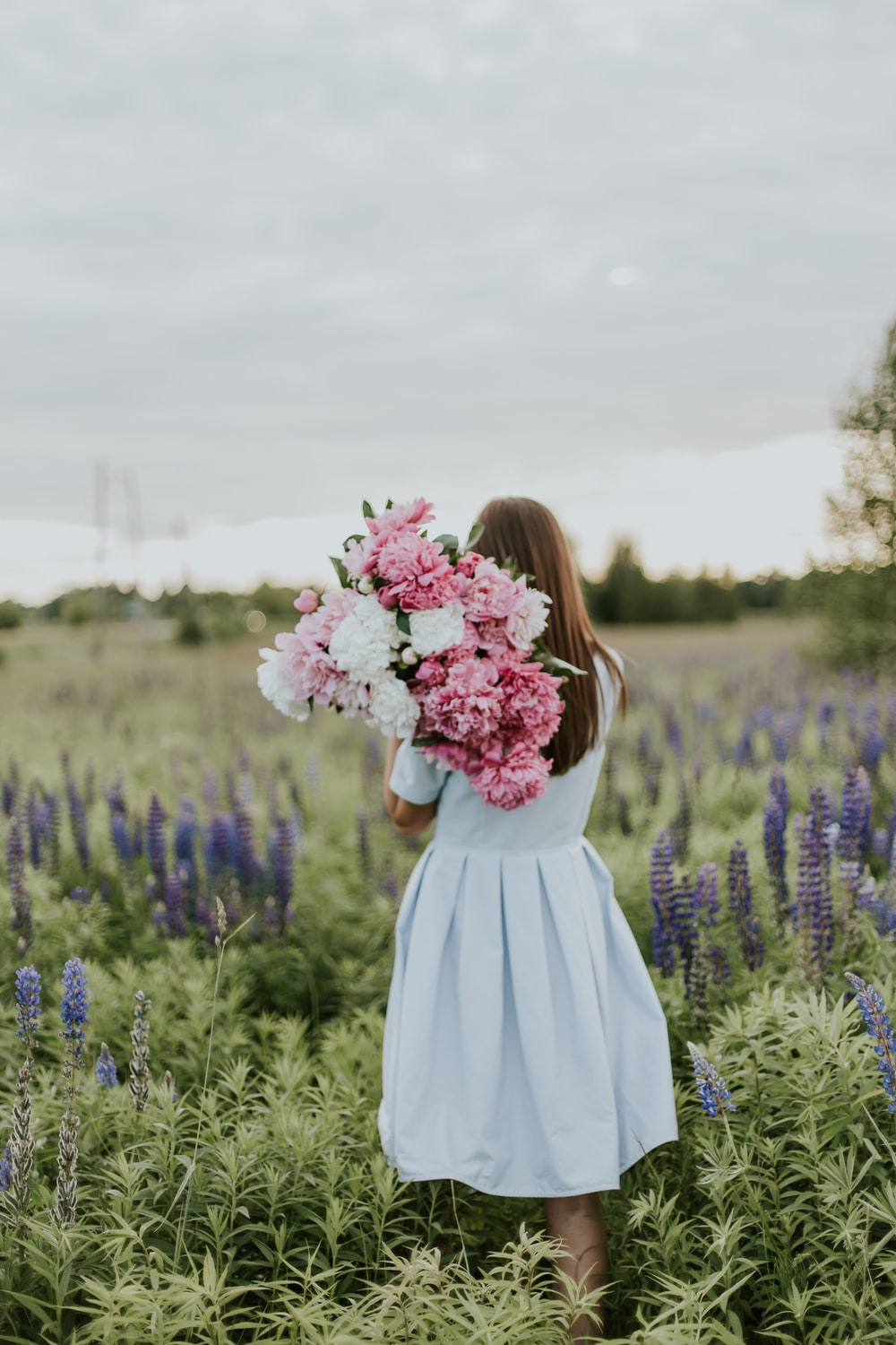 woman carrying pink and white flowers