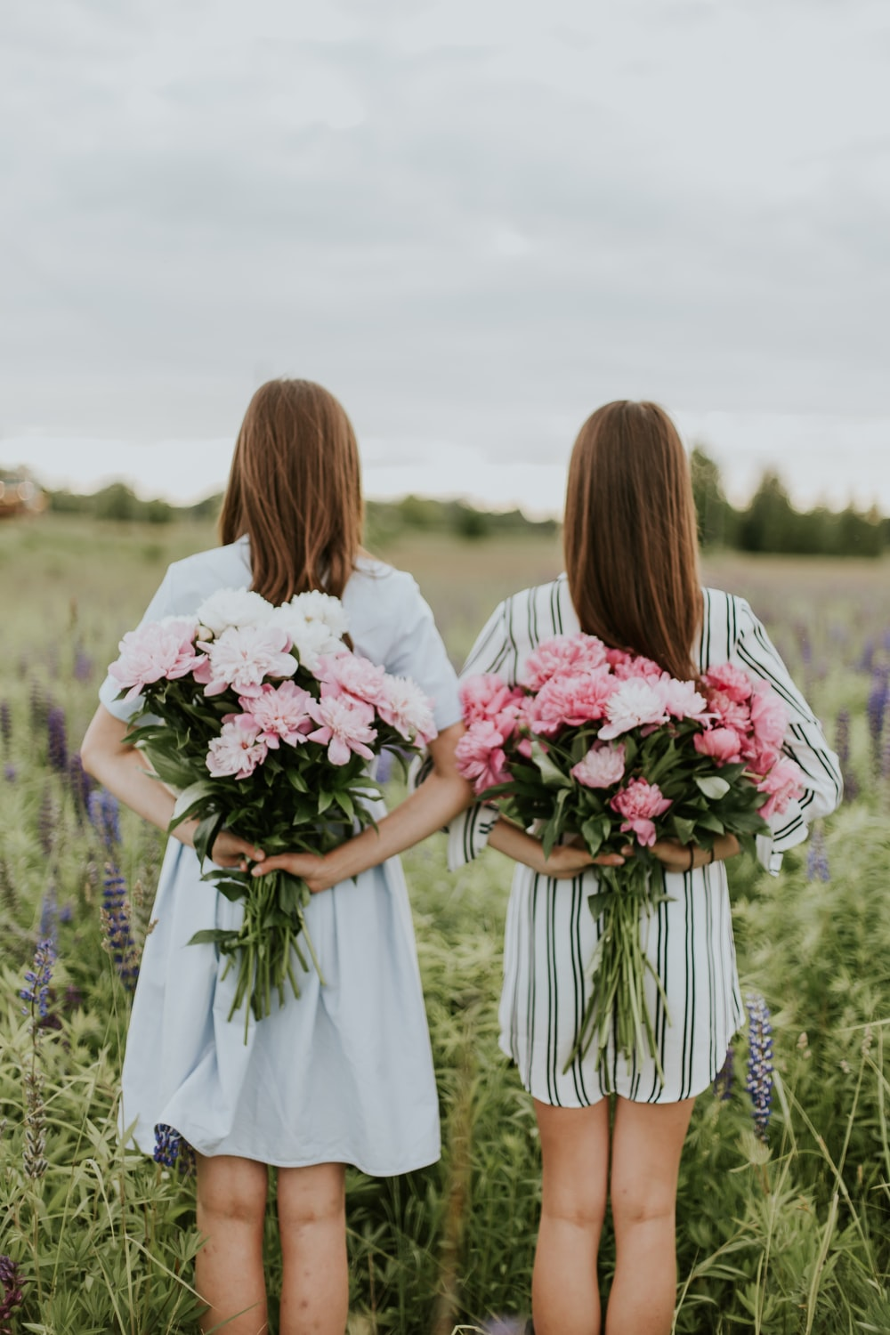 photo of two woman holding flower bouquets