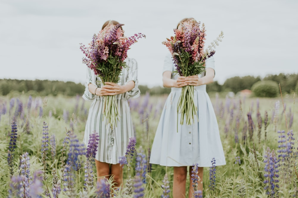 two woman holding pink petaled flowers