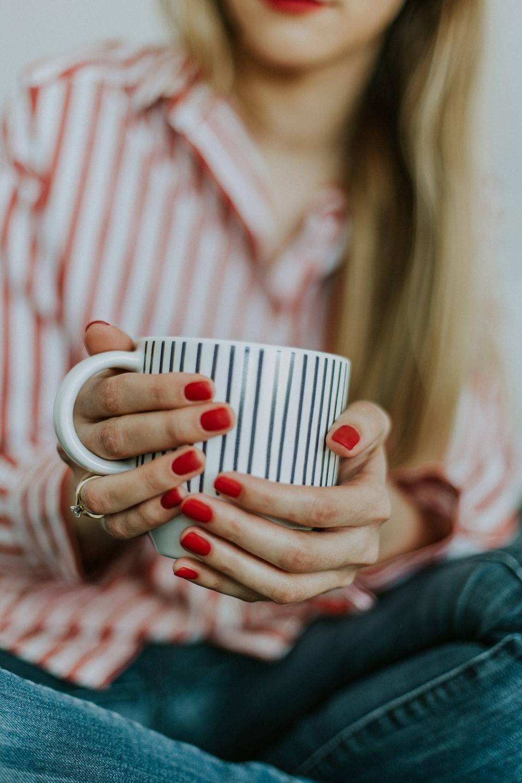 selective focus photo of a woman holding a white coffee mug