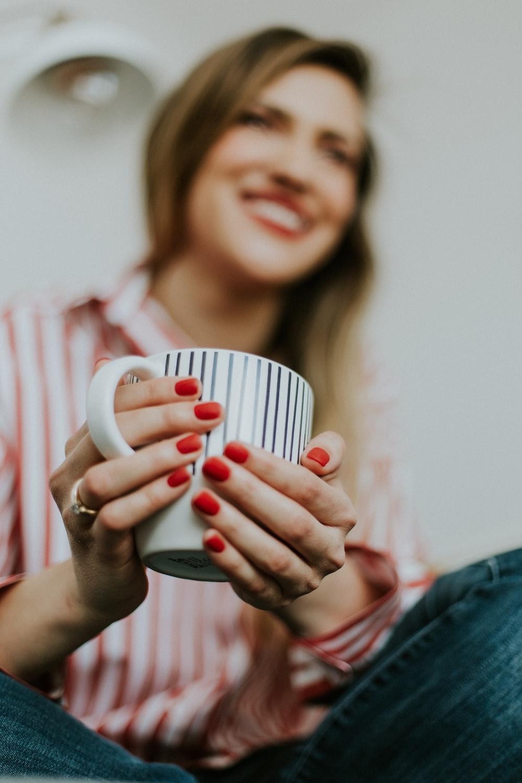 woman holding white and black ceramic mug