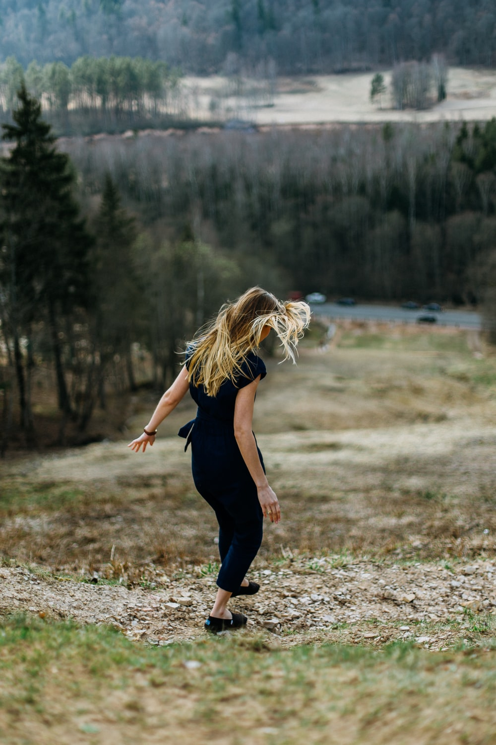 woman stepping on brown ground near road and cliff
