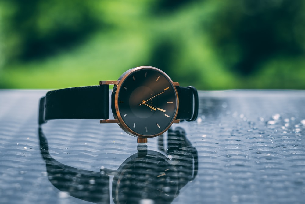 round gold-colored and black analog watch with link band