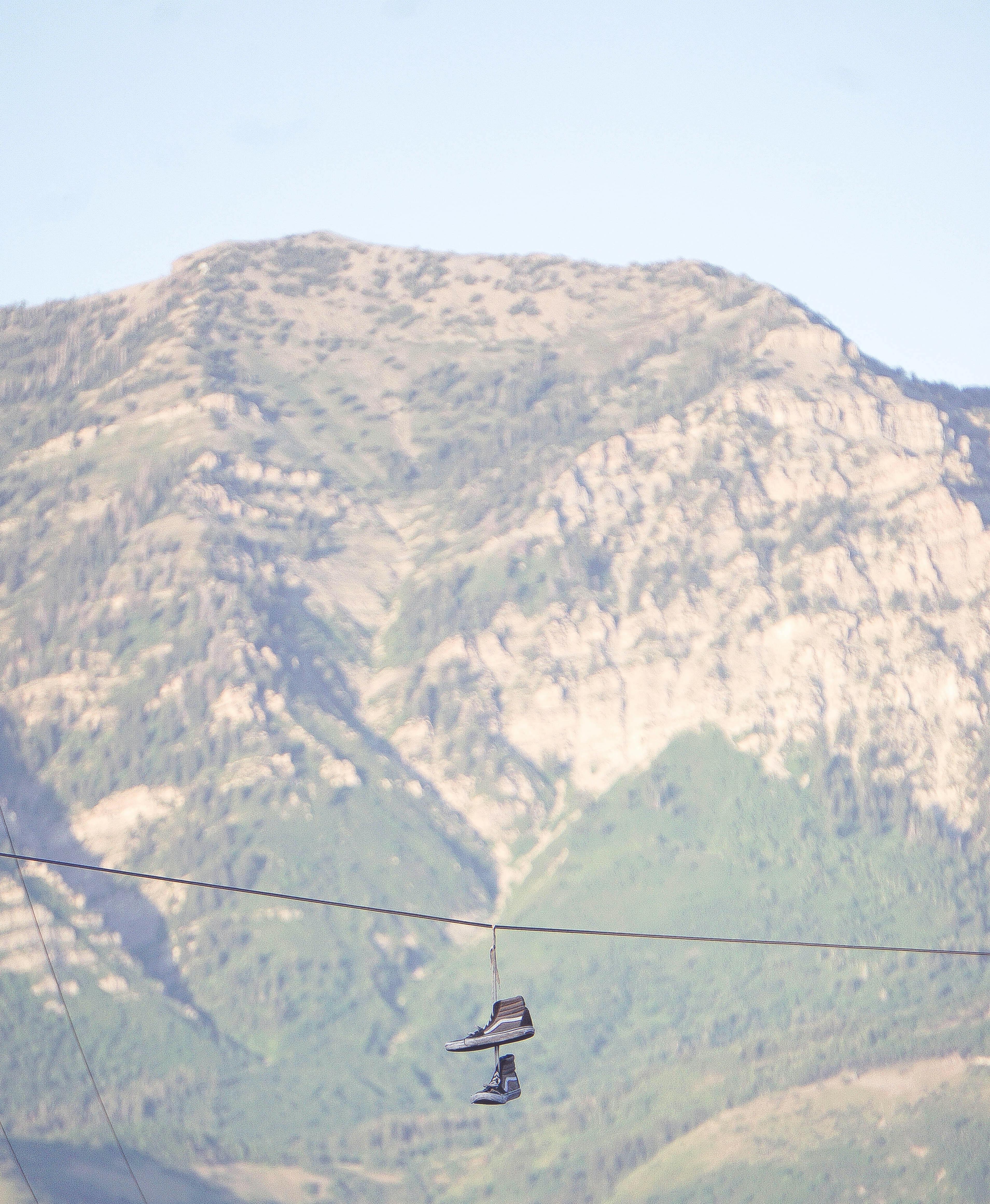 pair of brown Vans Sk8-Hi hanged on rope