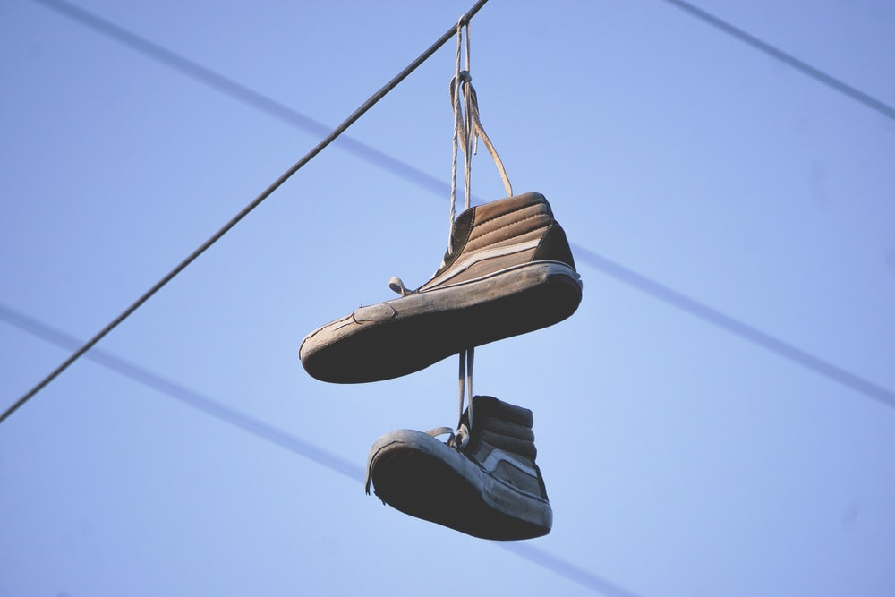 black-and-gray Vans Sk8-Hi sneakers hanged on electric wire