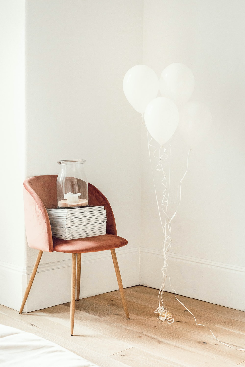 white balloons beside jar on book and chair