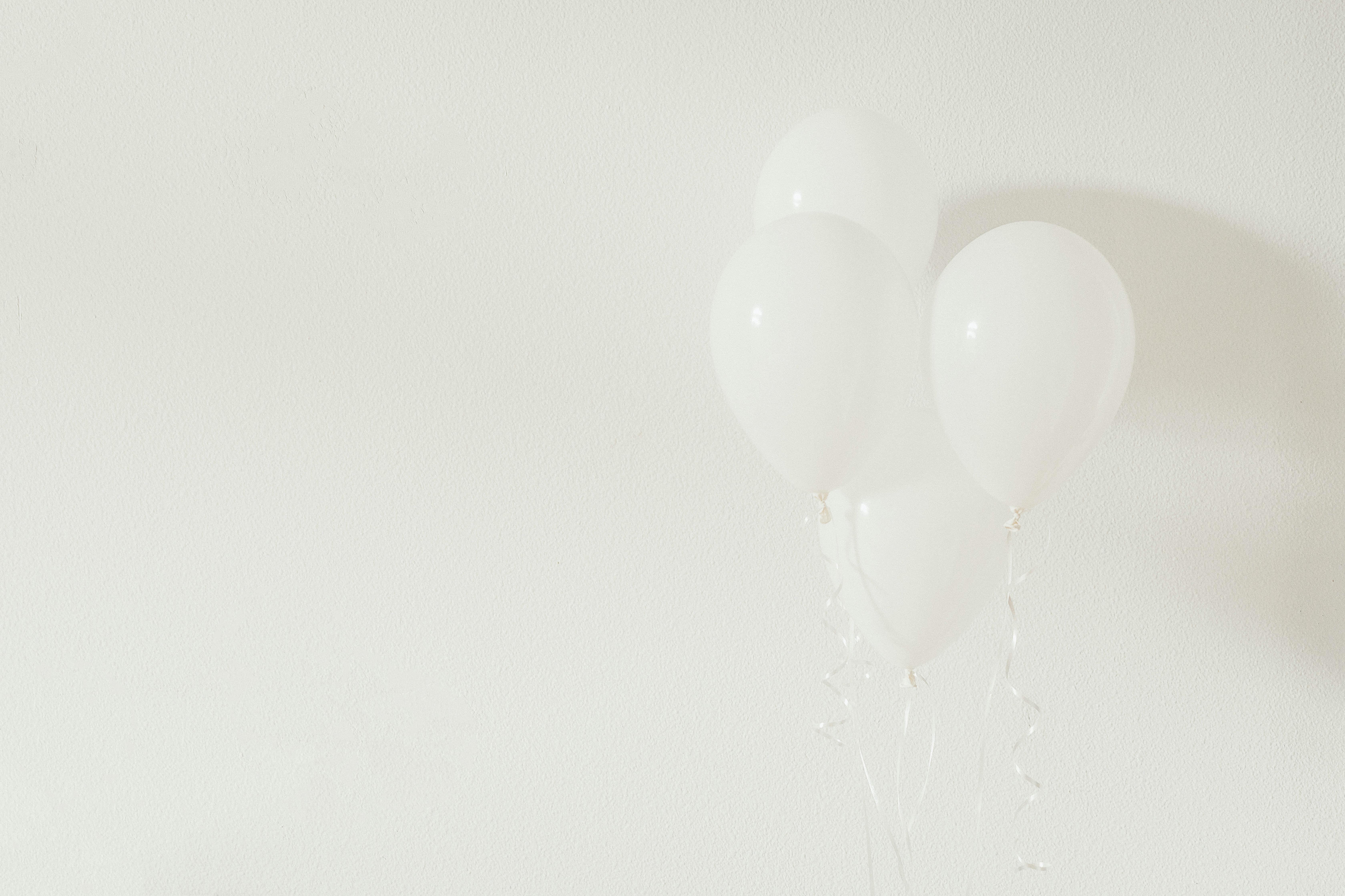 four white balloons on white wall
