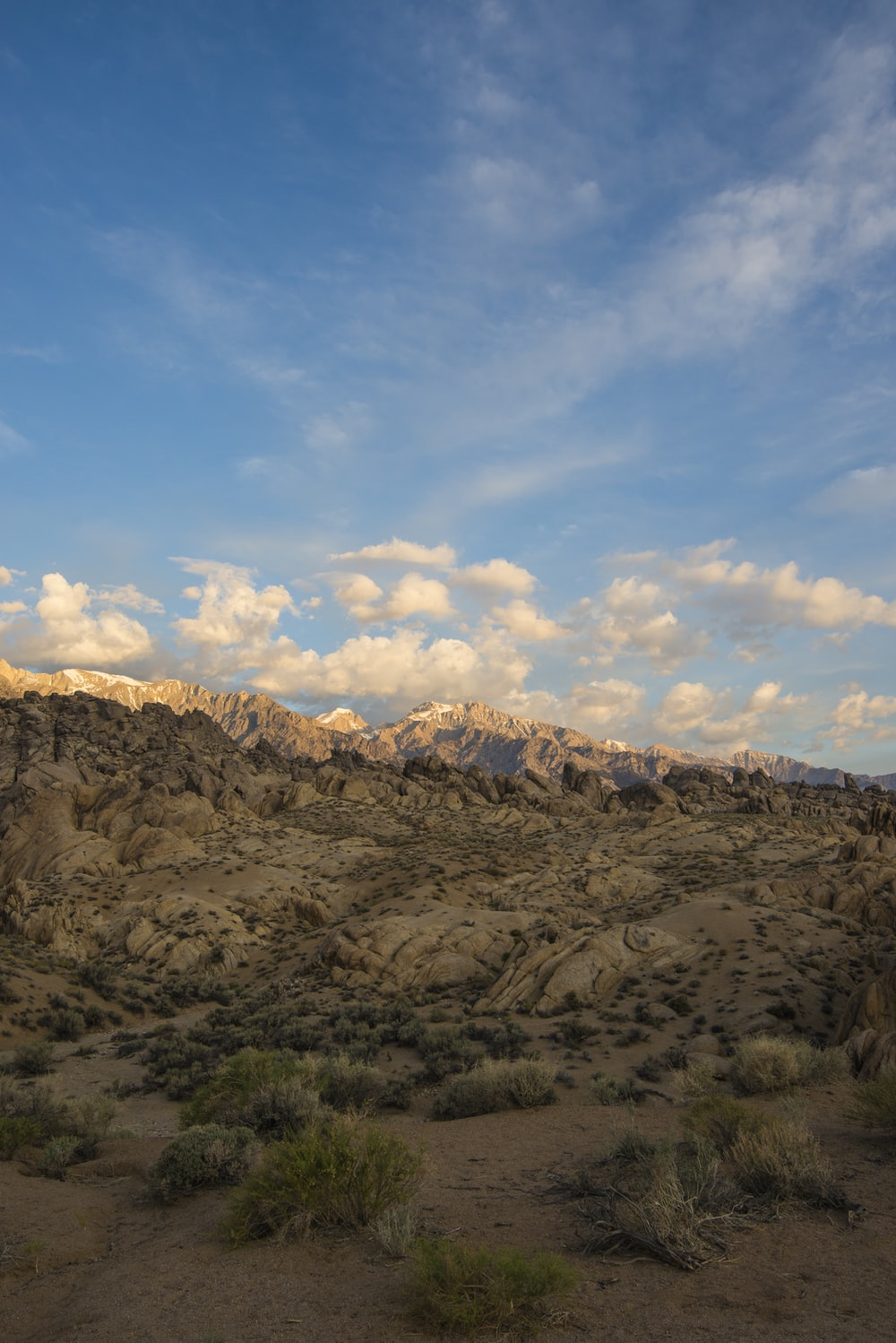 brown mountain under blue sky and white clouds during daytime