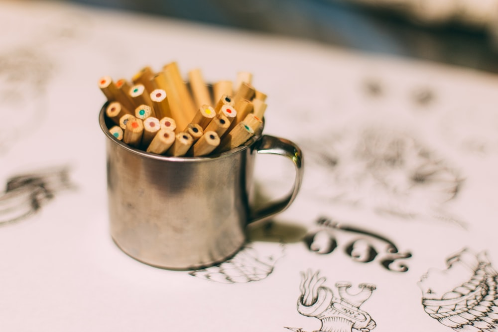 brown sticks in silver cup with handle