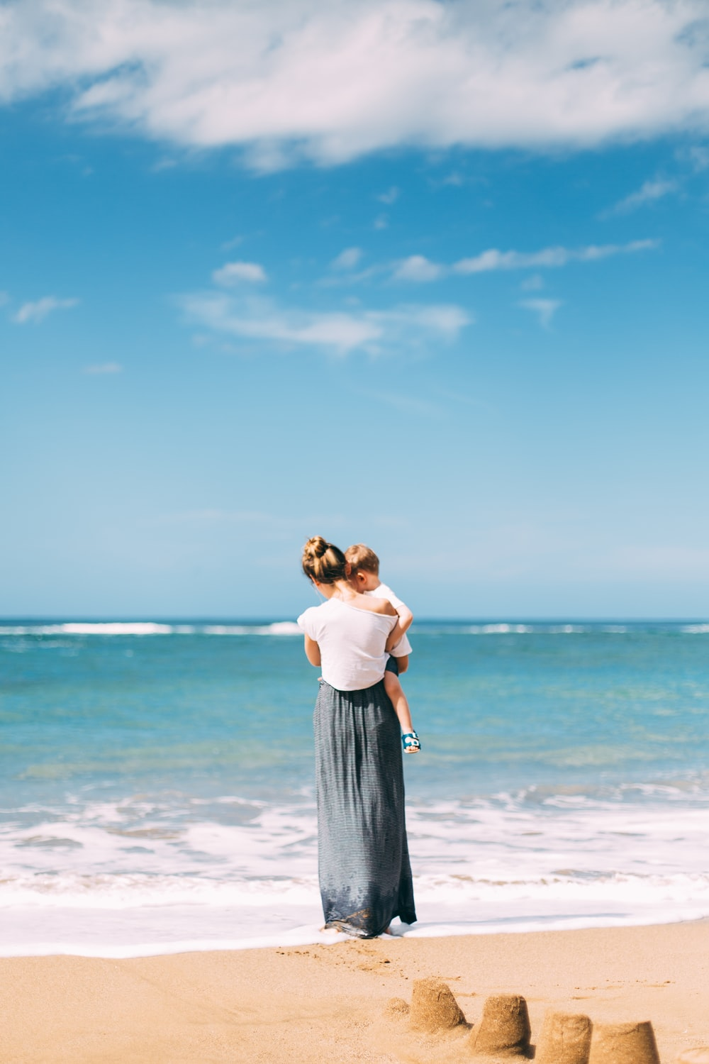 woman carrying toddler on seashore