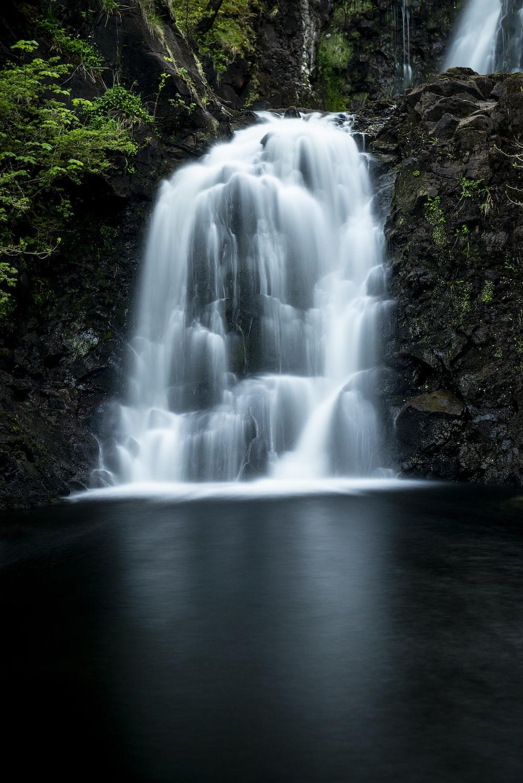 waterfall between brown soils