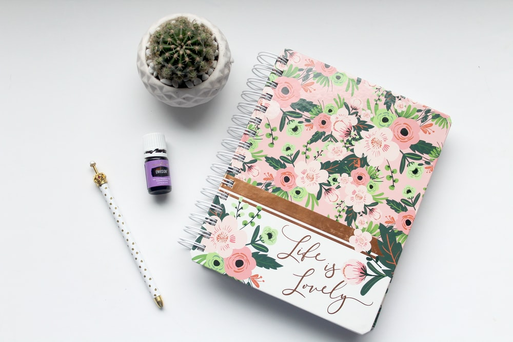 white and pink floral notebook on table