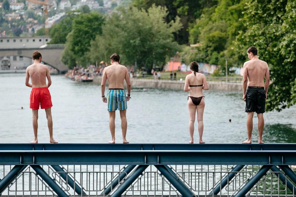 four people standing on bridge