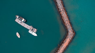 bird's eye view photography of boat near the coast drone view teams background