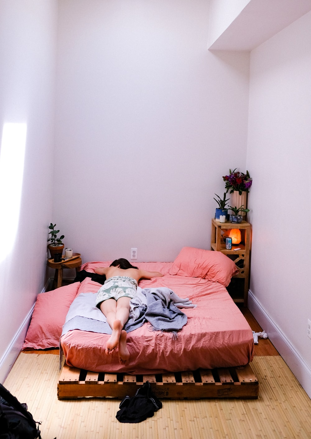 person lying on pink mattress