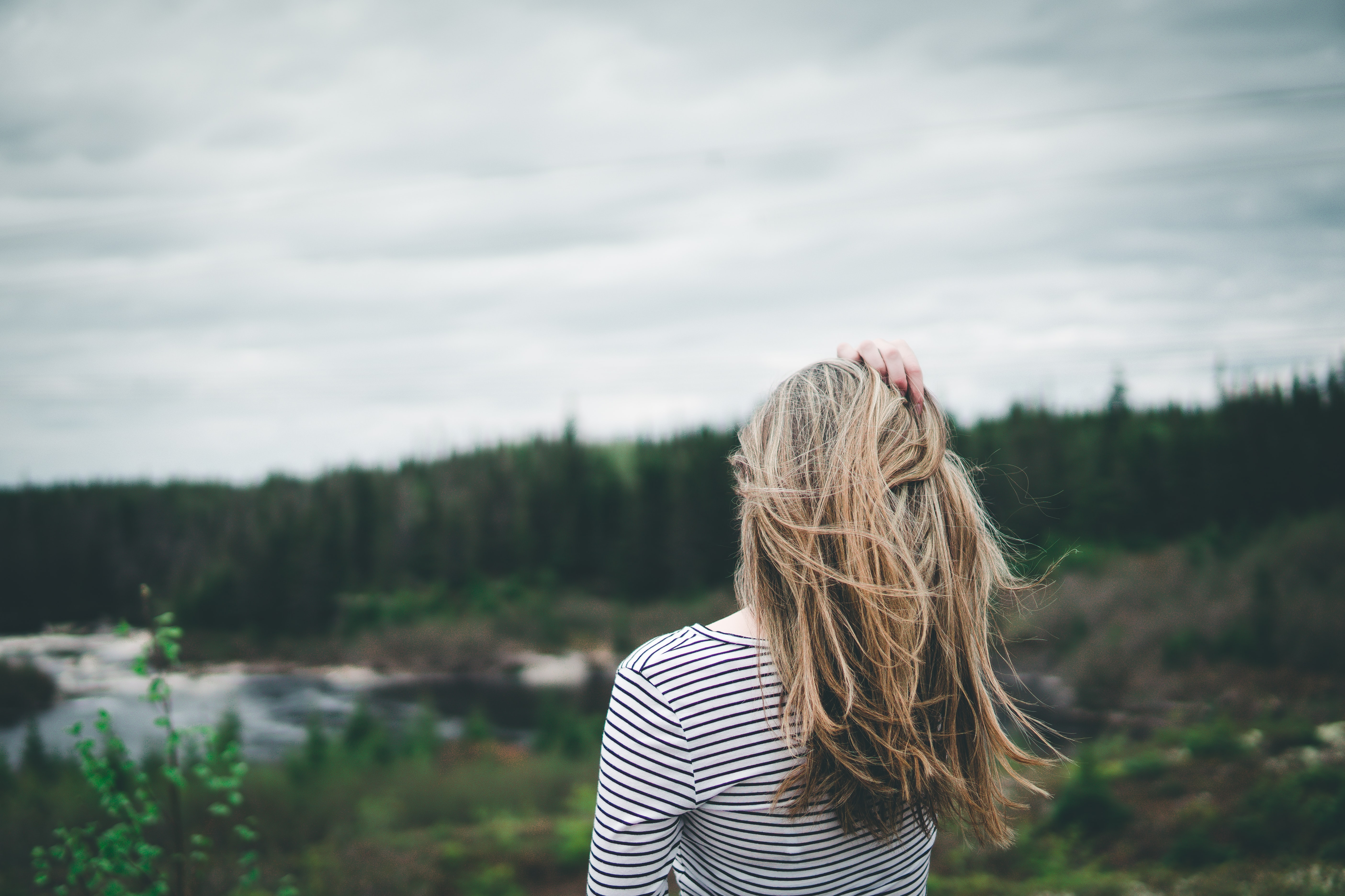 selective focus photography of woman wearing striped shirt facing forest