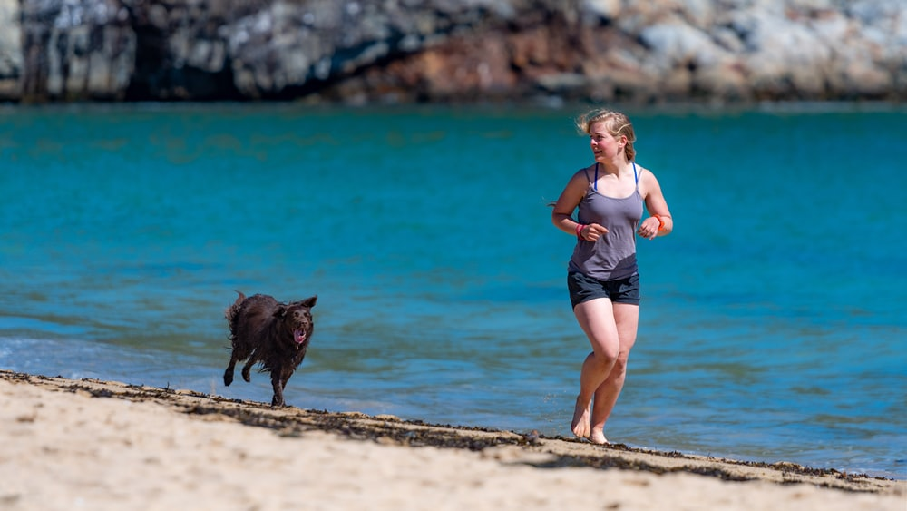 woman and dog running in seashore