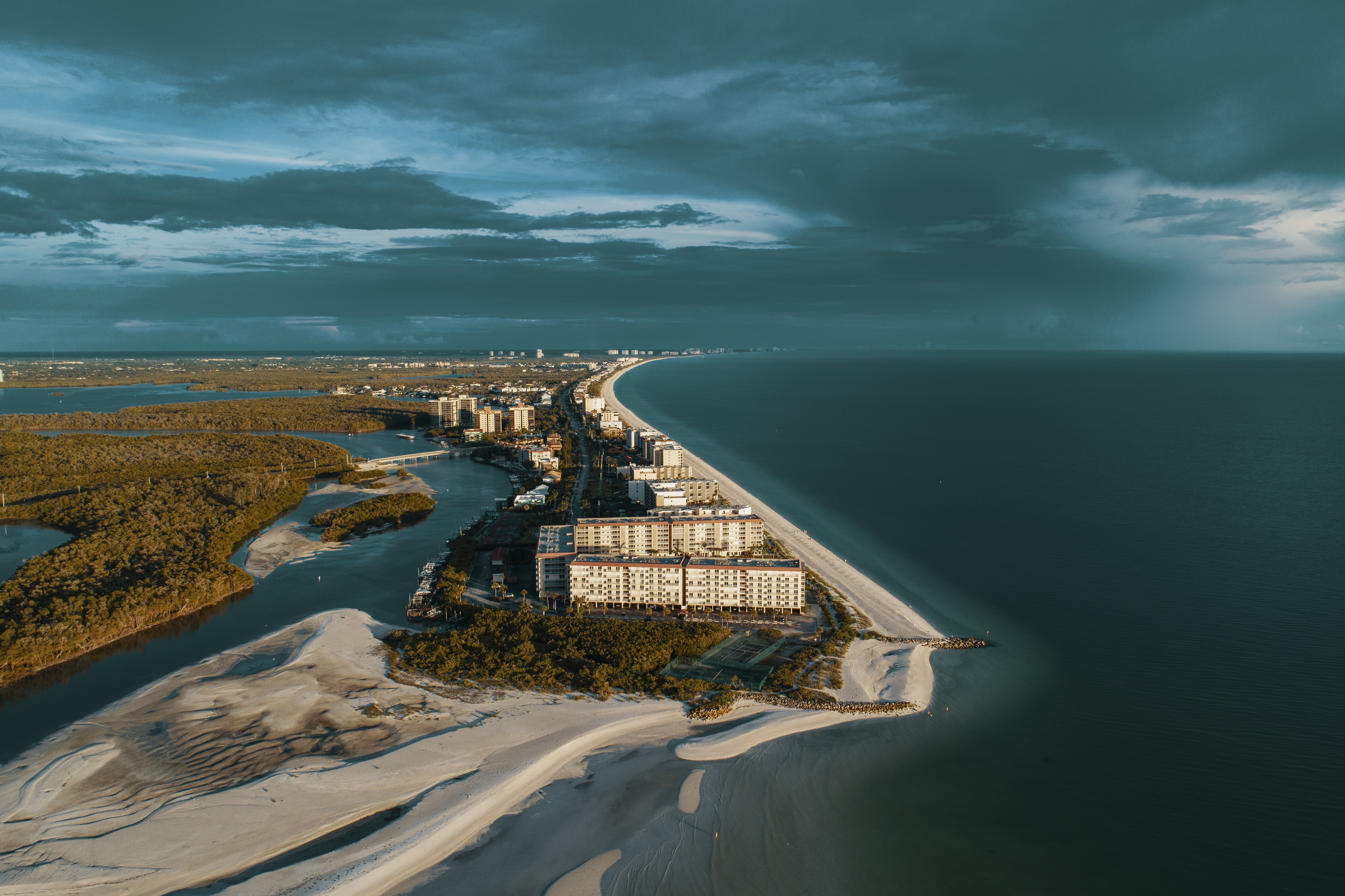aerial photography of white house beside ocean under gray clouds at daytime