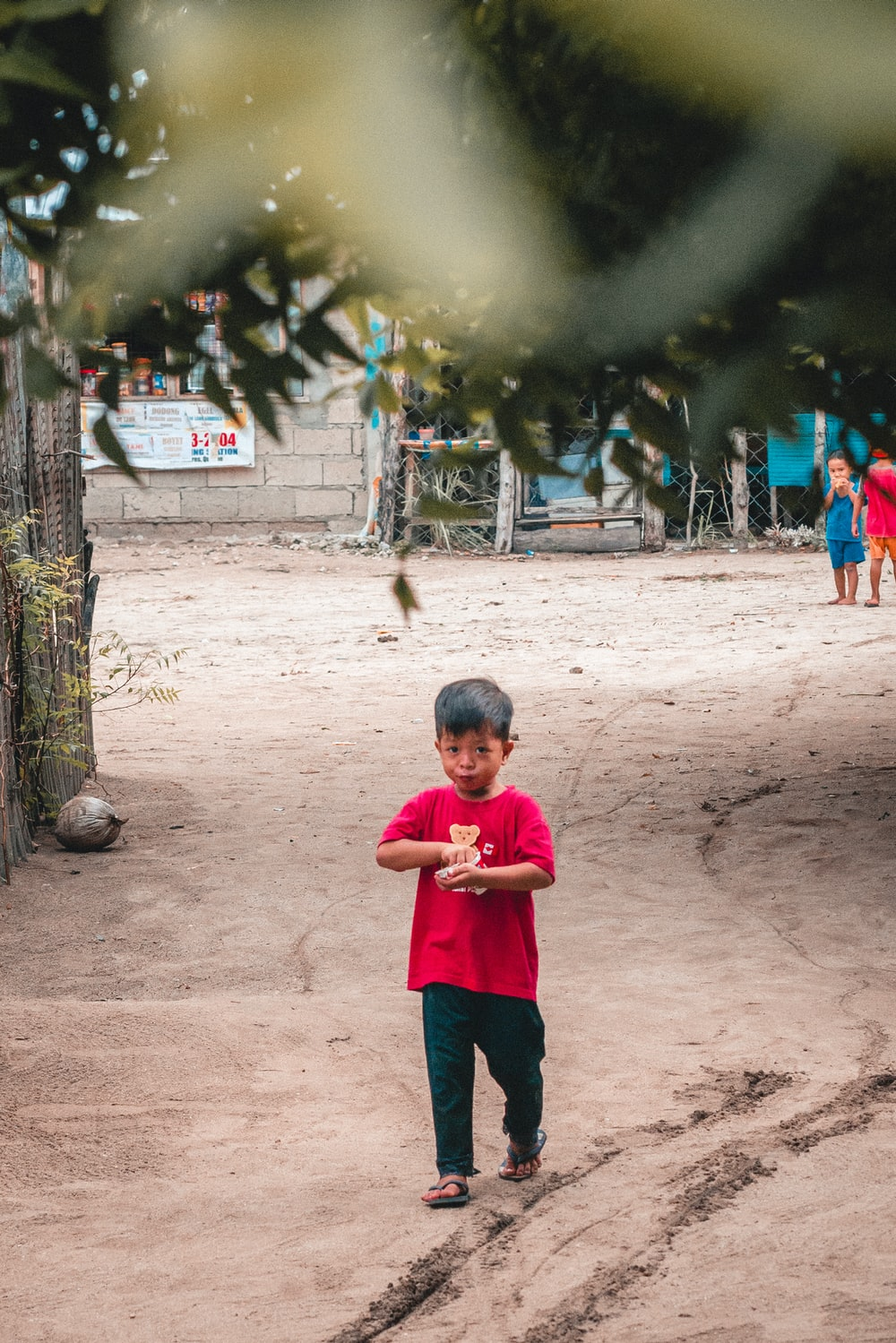 boy in pink shirt walking on dirt